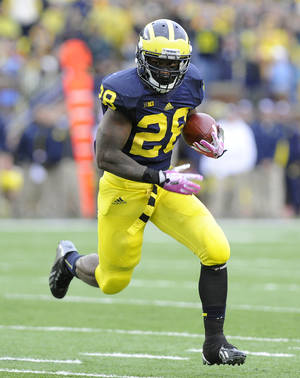 Photo - Michigan running back Fitzgerald Toussaint runs for a second quarter touchdown against Indiana during an NCAA football game at Michigan Stadium in Ann Arbor, Saturday, Oct. 19, 2013. (AP Photo/Lon Horwedel)
