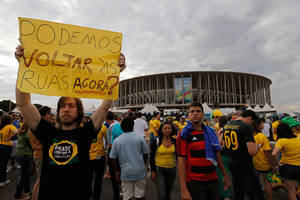 "Photo - A demonstrator shows poster written in Portuguese that reads, ""Can we go back to the streets now?"" during the third place finish World Cup match between Brazil and the Netherlands, outside the National Stadium in Brasilia, Brazil, Saturday, July 12, 2014. Robin van Persie and Daley Blind scored early goals to help give the Netherlands a 3-0 win over host Brazil in the third-place match at the World Cup. (AP Photo/Eraldo Peres)"