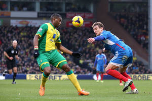 Photo - Norwich City's Sebastien Bassong, left, and Hull City's Nikica Jelavic battle for the ball during their English Premier League soccer match at Carrow Road, Norwich, England, Saturday, Jan. 18, 2014. (AP Photo/Chris Radburn, PA Wire)   UNITED KINGDOM OUT  -  NO SALES  -  NO ARCHIVES