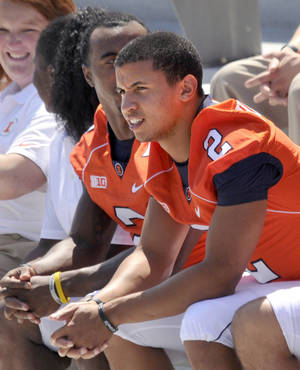 Photo - Illinois quarterback Nathan Scheelhaase, right, waits patiently with teammates, including V'Angelo Bentley, left, for a team photo during the team's NCAA college football media day at Memorial Stadium in Champaign, Ill., on Sunday, Aug. 11, 2013. (AP Photo/The News-Gazette, Heather Coit)