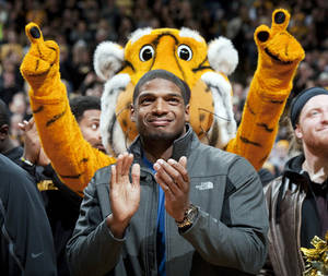 Photo - FILE - In this Feb. 15, 2014, file photo, Missouri's All-American defensive end Michael Sam claps during the Cotton Bowl trophy presentation at halftime of an NCAA college basketball game between Missouri and Tennessee in Columbia, Mo.  Sam has been selected the winner of the Arthur Ashe Courage Award. The Missouri defensive end who likely will be drafted by an NFL team this weekend, will receive the award given to individuals who transcend sports at The 2014 ESPYs on July 16. (AP Photo/L.G. Patterson, File)