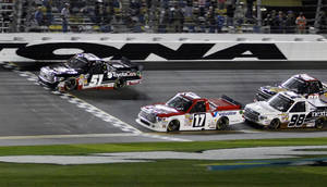 Photo - Kyle Busch (51) crosses the finish line ahead of Timothy Peters (17) to win the NASCAR Truck Series auto race at Daytona International Speedway in Daytona Beach, Fla., Friday, Feb. 21, 2014. (AP Photo/Terry Renna)
