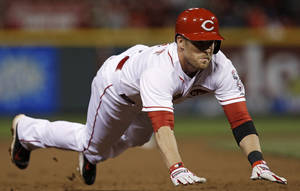 Photo - Cincinnati Reds' Zack Cozart dives into third base with a triple off Chicago Cubs starting pitcher Jeff Samardzija in the sixth inning of a baseball game, Tuesday, April 29, 2014, in Cincinnati. Cozart scored later in the inning. (AP Photo)