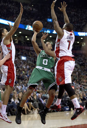 Photo - Boston Celtics guard Avery Bradley (0) shoots under pressure from Toronto Raptors forward Landry Fields, left, and guard Kyle Lowry during the first half of an NBA basketball game Wednesday, Oct. 30, 2013, in Toronto. (AP Photo/The Canadian Press, Frank Gunn)