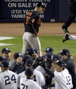 Photo -   Baltimore Orioles' Matt Wieters, top, heads off the field as the New York Yankees celebrate their victory in game 5 of the American League division baseball series on Friday, Oct. 12, 2012, in New York. The Yankees won the game 3-1 and advanced to the AL championship. (AP Photo/Peter Morgan)