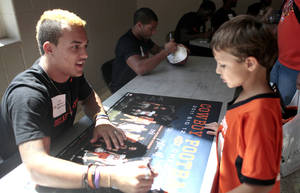 Photo - OKLAHOMA STATE UNIVERSITY / OSU / COLLEGE FOOTBALL / CHILD / CHILDREN / KIDS: Oklahoma State football player Dominic Ramacher signs a poster for Eli Farrow during Oklahoma State's Fan Appreciation Day at Gallagher-Iba Arena in Stillwater, Okla., Saturday, Aug. 4, 2012. Photo by Sarah Phipps, The Oklahoman