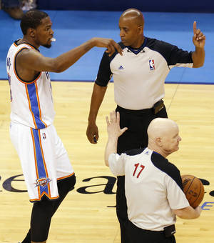 Photo - Oklahoma City's Kevin Durant (35) signals for Serge Ibaka's final shot to count to officials Joe Crawford (17) and Derrick Stafford (7) after overtime in Game 5 in the first round of the NBA playoffs between the Oklahoma City Thunder and the Memphis Grizzlies at Chesapeake Energy Arena in Oklahoma City, Tuesday, April 29, 2014. Ibaka's shot was shown on instant replay to be after the buzzer. Memphis won 100-99 in overtime. Photo by Nate Billings, The Oklahoman
