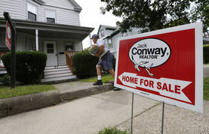 Photo - In this July 10, 2014 photo, a mailman delivers mail to a house for sale in Quincy, Mass. Freddie Mac reports on average U.S. mortgage rates for this week on Thursday, Sept. 4, 2014 (AP Photo/Michael Dwyer)