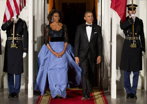 Photo - FILE - This Feb. 11, 2014 file photo shows President Barack Obama and first lady Michelle Obama arrive at the North Portico of the White House in Washington to greet French President François Hollande, who is arriving for a State Dinner. (AP Photo/ Evan Vucci, File)