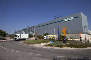 Photo - Trucks run past Teva Pharmaceutical Logistic Center in the town of Shoam, Israel, Wednesday, Oct. 16, 2013. As the world's leading maker of generic drugs, Teva Pharmaceutical Industries Ltd. has evolved not only into a giant in the pharmaceutical world but also a source of pride for Israel. Now, following an announcement of planned layoffs and revelations it enjoys sweeping tax exemptions, this homegrown jewel of the Israeli economy is on the defensive and fighting to save its reputation as the country's flagship company. (AP Photo/Dan Balilty)