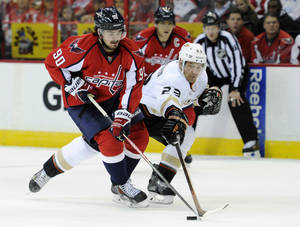 Photo - Washington Capitals center Marcus Johansson (90), of Sweden, battles for the puck against Anaheim Ducks defenseman Francois Beauchemin (23) during the first period of an NHL hockey game, Monday, Dec. 23, 2013, in Washington. (AP Photo/Nick Wass)