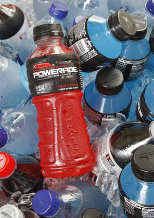 Photo - FILE - In this Aug. 5, 2010 file photo, bottles of Powerade sports drink and other Coca-Cola products are chilled over ice in Orlando, Fla. A controversial ingredient, brominated vegetable oil, is being removed from some Powerade sports drinks. (AP Photo/Jon Elswick, File)