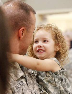 Photo - Two-year-old Hadlee Walker looks into the eyes of her father, Sgt. First Class Chad Walker, as the Oklahoma National Guard welcomes 64 members of the 2-45th Agri-business Development Team home from a 10-month deployment to Afghanistan, during a ceremony Saturday afternoon at the Norman Armed Forces Reserve Center. By Paul Hellstern, The Oklahoman ORG XMIT: KOD <strong>PAUL HELLSTERN</strong>