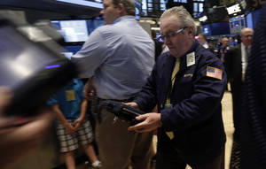 Photo - Trader James Dresch, right, works on the floor of the New York Stock Exchange, Monday, June 30, 2014.  European stocks were lower Wednesday July 30, 2014 ahead of U.S. economic data while cheery earnings from major Japanese companies such as Honda Motor Co. boosted Asian markets.(AP Photo/Richard Drew)