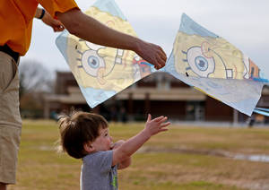 Photo - Evan Baker, 1, and his father, Brandon Baker, get ready to fly kites Friday during a Basant Kite Festival at the University of Central Oklahoma. PHOTOS BY BRYAN TERRY, THE OKLAHOMAN