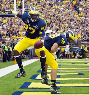 Photo - Michigan tight end Devin Funchess (87) celebrates his touchdown with tight end Jake Butt (88) in the second quarter of an NCAA college football game against Minnesota, Saturday, Oct. 5, 2013, in Ann Arbor, Mich. (AP Photo/Tony Ding)