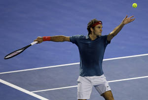 Photo - Roger Federer of Switzerland  serves to Jo-Wilfried Tsonga of France during their fourth round match at the Australian Open tennis championship in Melbourne, Australia, Monday, Jan. 20, 2014.(AP Photo/Aijaz Rahi)