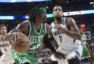 Photo - Boston Celtics' Gerald Wallace, left, drives to the net as Minnesota Timberwolves' Derrick Williams defends during the second quarter of an NBA preseason basketball game in Montreal, Sunday, Oct. 20, 2013. (AP Photo/The Canadian Press, Graham Hughes)