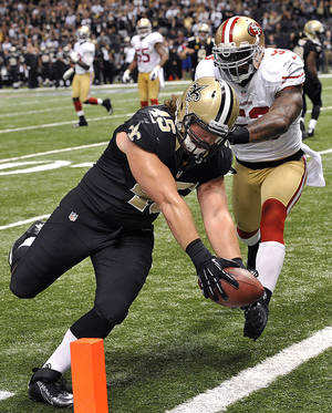 Photo -   New Orleans Saints fullback Jed Collins (45) scores a touchdown as San Francisco 49ers inside linebacker NaVorro Bowman (53) covers in the second half of an NFL football game in New Orleans, Sunday, Nov. 25, 2012. (AP Photo/Bill Feig)