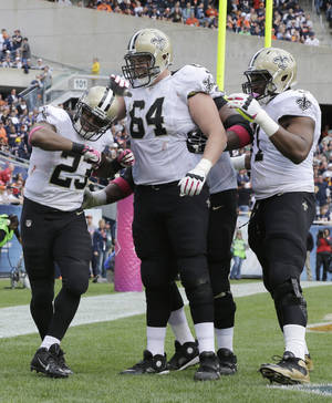 Photo - New Orleans Saints running back Pierre Thomas (23) celebrates his touchdown with his teammates during the first half of an NFL football game against the Chicago Bears, Sunday, Oct. 6, 2013, in Chicago.(AP Photo/Nam Y. Huh)