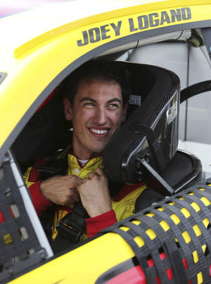 Photo - Joey Logano smiles after qualifying for the NASCAR Sprint Cup Series auto race at Michigan International Speedway in Brooklyn, Mich., Friday, Aug. 16, 2013. Logano won the pole. (AP Photo/Bob Brodbeck)