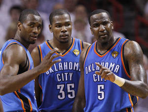 Photo - Oklahoma City Thunder power forward Serge Ibaka (9) from Republic of Congo, small forward Kevin Durant (35) and center Kendrick Perkins (5) react during the first half at Game 5 of the NBA finals basketball series against the Miami Heat, Thursday, June 21, 2012, in Miami. (AP Photo/Lynne Sladky)