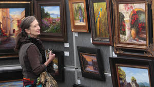 Photo - Dottie Gourley looks over the paintings of Janet Loveless at the Downtown Edmond Arts Festival. Photo By David McDaniel, The Oklahoman <strong>David McDaniel - The Oklahoman</strong>