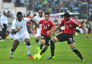 Photo - Ghana's Asamoah Gyan, left, battles with Egypt's Mohamed Naguib and Ahmed Shedid, right, during their World Cup playoff soccer match in Kumasi, Ghana, Tuesday, Oct. 15, 2013. Ghana stunned Egypt 6-1 in the first leg of their World Cup playoff on Tuesday, with Gyan's fifth-minute goal kicking off a dominant performance that makes the Black Stars overwhelming favorites to be one of the five African teams in Brazil next year. (AP Photo)