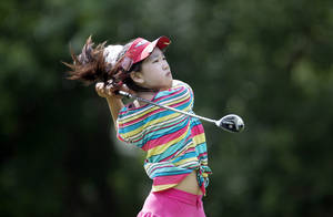 Photo - ADVANCE FOR WEEKEND EDITIONS JUNE 14-15 - FILE - This June 19, 2013 file photo provided by the USGA shows Lucy Li hitting a tee shot on the sixth hole during the first round of the 2013 U.S. Women's Public Links golf event in Norman, Okla. Li, the 11-year-old from the suburbs south of San Francisco became the youngest player to qualify for the U.S. Women's Open by winning the sectional at Half Moon Bay in California by seven strokes last month.  (AP Photo/USGA, Joel Kowsky, file)