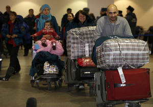 photo - Russian-Syrian family leave passport control zone just after their arrival from Beirut in Moscow Domodedovo airport, Russia, Wednesday, Jan. 23, 2013. The Kremlin's evacuation of Russians from Syria on Tuesday marks a turning point in its view of the civil war, representing increasing doubts about Bashar Assad's hold on power and a sober understanding that it has to start rescue efforts before it becomes too late. The operation has been relatively small-scale - involving fewer than 100 people, mostly women and children - but it marks the beginning of what could soon turn into a risky and challenging operation.  (AP Photo/Alexander Zemlianichenko)