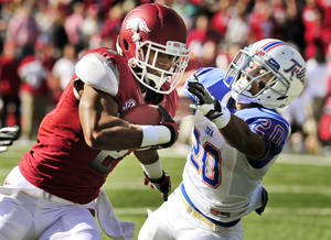 photo -   Arkansas wide receiver Julian Horton (2) tries to get around Tulsa defensive back Marco Nelson (20) during the first quarter of an NCAA college football game in Fayetteville, Ark., Saturday, Nov. 3, 2012. (AP Photo/April L. Brown)