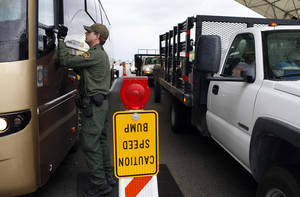 Photo - FILE - This July 29, 2010 file photo shows a Border Patrol agent checking the identification card of a bus driver at a checkpoint in Amado, Ariz. The American Civil Liberties Union reported Wednesday Jan. 15, 2014 that border patrol agents at checkpoints across southern Arizona are routinely violating the constitutional rights of U.S. residents, including unjustified detentions and illegal searches as a pretext to investigating other criminal activity in violation of the agency's mandate that stops be limited to inquiring about citizenship and visually inspecting vehicles.  (AP Photo/Jae C. Hong, file)