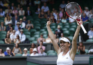 Photo - Simona Halep of Romania celebrates as she defeats Sabine Lisicki of Germany in their women's singles quarterfinal match at the All England Lawn Tennis Championships in Wimbledon, London, Wednesday, July 2, 2014. (AP Photo/Pavel Golovkin)