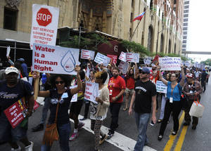 Photo - Protesters march over the controversial water shut-offs Friday, July 18, 2014, in Detroit, Mich.  (AP Photo/Detroit News, David Coates)