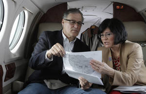 Photo - Washington Gov. Jay Inslee, left, looks at a map with Dept. of Ecology Director Maia Bellon, right, Wednesday, March 6, 2013, as they fly to Richland, Wash. to tour the Hanford Nuclear Reservation and meet with Dept. of Energy officials in order to learn more about tanks on the site that are leaking radioactive waste. (AP Photo/Ted S. Warren)