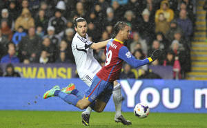 Photo - Swansea City' Chico Flores, left, and Crystal Palace's Marouane Chamakh in action during their English Premier League soccer match at the Liberty Stadium, Swansea, Wales, Sunday, March 3, 2014. (AP Photo/PA)    UNITED KINGDOM OUT    -   NO SALES   -   NO ARCHIVES