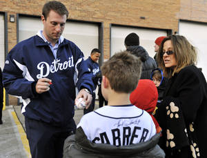photo - Detroit Tigers' Max Scherzer hands a signed ball to Ben Gerhard, 10, with his mother Julie Martin, right, as the baseball team visits Royal Oak Fire Station No. 2 as part of the Tigers Winter Caravan, Thursday, Jan. 24, 2013, in Royal Oak, Mich. (AP Photo/Detroit News, Robin Buckson)  DETROIT FREE PRESS OUT; HUFFINGTON POST OUT
