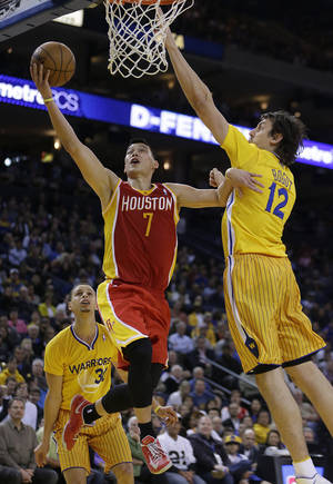 Photo - Houston Rockets' Jeremy Lin (7) lays up a shot against Golden State Warriors' Andrew Bogut (12) during the second half of an NBA basketball game Friday, March 8, 2013, in Oakland, Calif. The Rockets won 94-88. (AP Photo/Ben Margot)