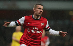 Photo - Arsenal's Lukas Poldoski celebrates after scoring the opening goal during their fourth round English FA Cup soccer match between Arsenal and Coventry City at the Emirates stadium in London, Friday, Jan.  24, 2014. (AP Photo/Alastair Grant)