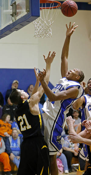 photo - HIGH SCHOOL BASKETBALL: Coyle's Tony Aska puts up a shot in front of Mulhall-Orlando's Ryon Boatright in Coyle, Okla., Tuesday, Jan. 22, 2013. Coyle High School hosted its final regular season basketball game in its current gym which was finished in 1939.  Photo by Bryan Terry, The Oklahoman