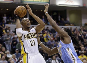 Photo - Indiana Pacers forward David West (21) shoots over Denver Nuggets forward Kenneth Faried in the second half of an NBA basketball game in Indianapolis, Monday, Feb. 10, 2014. The Pacers defeated the Nuggets 119-80.  (AP Photo/Michael Conroy)