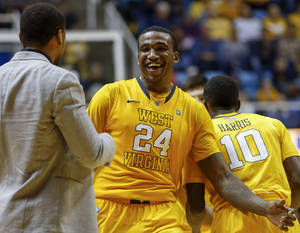 Photo - West Virginia's Aaric Murray (24) celebrates with players and coaches on the bench near the end of the second half of an NCAA college basketball game against Radford at WVU Coliseum in Morgantown, W.Va., Saturday, Dec. 22, 2012. WVU defeated Radford 72-62. (AP Photo/David Smith)