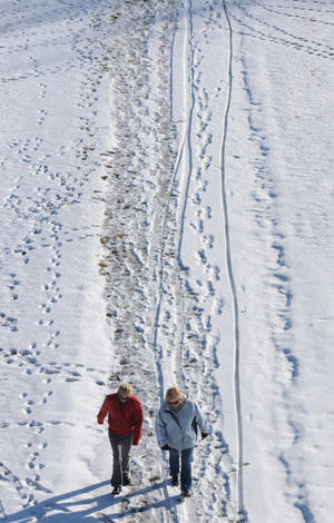 Photo - Two women stroll along a snow-covered path in downtown St. Joseph, Mich., Saturday, Dec. 28, 2013. (AP Photo/The Herald-Palladium, Don Campbell)