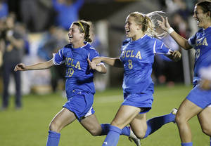Photo - UCLA players, from left, Chelsea Stewart, Abby Dahlkemper and Kodi Lavrusky celebrate after UCLA beat Virginia in penalty kicks in an NCAA college soccer semifinal match at the Women's College Cup tournament in Cary, N.C., Friday, Dec. 6, 2013. (AP Photo/Ellen Ozier)