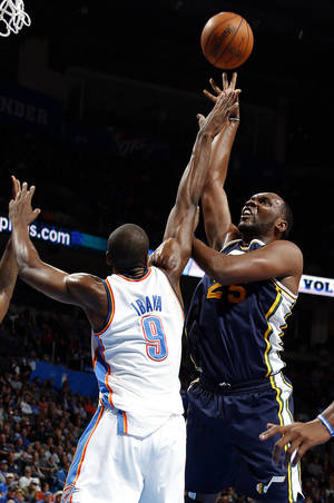 Photo - Oklahoma City's Serge Ibaka (9) defends against Utah's Al Jefferson (25) during the NBA game between the Oklahoma City and the Utah Jazz and the Chesapeake Energy Arena, Friday,Nov. 30, 2012. Photo by Sarah Phipps, The Oklahoman