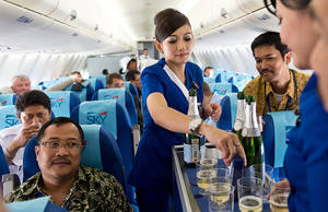 Photo -   In this photo released by Sergey Dolya, cabin crew serve passengers during a flight over Jakarta, Indonesia, Wednesday, May 9, 2012. The Russian-made Sukhoi jet plane with 50 people on board, including eight Russians and an American, has gone missing during the second demonstration flight of the day near Jakarta, Indonesian government officials said Wednesday.(AP Photo/Sergey Dolya) NO SALES