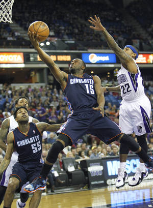 Photo - Charlotte Bobcats guard Kemba Walker (15) drives to the basket against Sacramento Kings defender Isaiah Thomas (22) during the first half of an NBA basketball game in Sacramento, Calif., on Saturday, Jan. 4, 2014. (AP Photo/Steve Yeater)