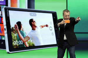 Photo - Stepen Elop, executive vice president of Nokia, demonstrates the picture taking ability of the new Nokia Lumia 930 phone during a keynote address of the Microsoft Build Conference Wednesday, April 2, 2014, in San Francisco. Microsoft kicked off its annual conference for software developers, with new updates to the Windows 8 operating system and upcoming features for Windows Phone and Xbox. (AP Photo/Eric Risberg)