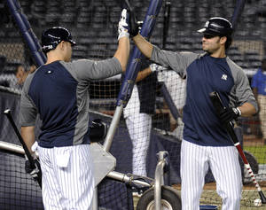 Photo -   New York Yankees' Nick Swisher, right, and Russell Martin high-five during baseball practice Friday, Oct. 5, 2012, at Yankee Stadium in New York for the American League division series. (AP Photo/Bill Kostroun)