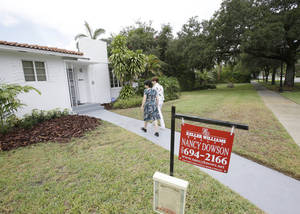 Photo - In this Thursday, May 29, 2014 photo, real estate broker Nancy Dowson, center right, with Keller Williams Realty, shows a house to prospective buyer Mary Tuttle, center, in Miami Shores, Fla. Freddie Mac releases weekly mortgage rates on Thursday, June 12, 2014. (AP Photo/Wilfredo Lee)
